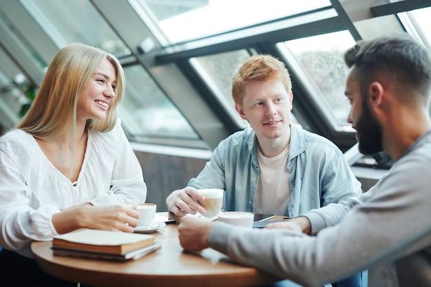 Grupo de felizes amigos de faculdade casuais sentados à mesa no café depois das aulas, tomando um café e discutindo planos para a semana