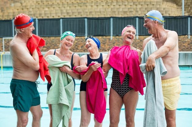 Grupo de felizes nadadores sêniors limpando o corpo com toalhas à beira da piscina