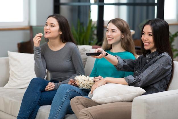 Grupo de fêmeas adultas assistindo tv juntos