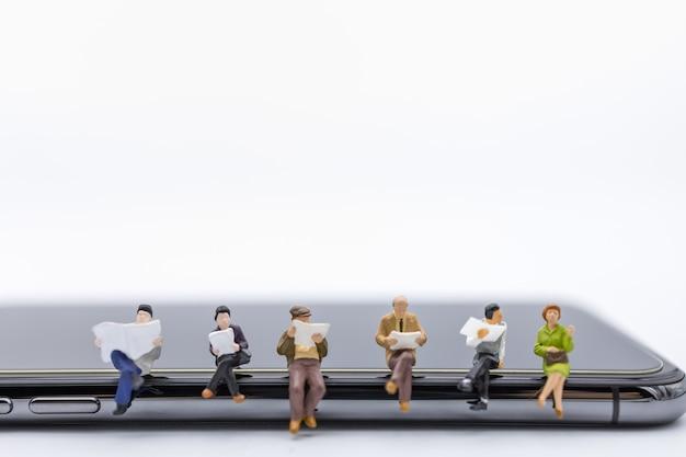Grupo de figura em miniatura de empresário sentado e lendo no telefone móvel esperto.