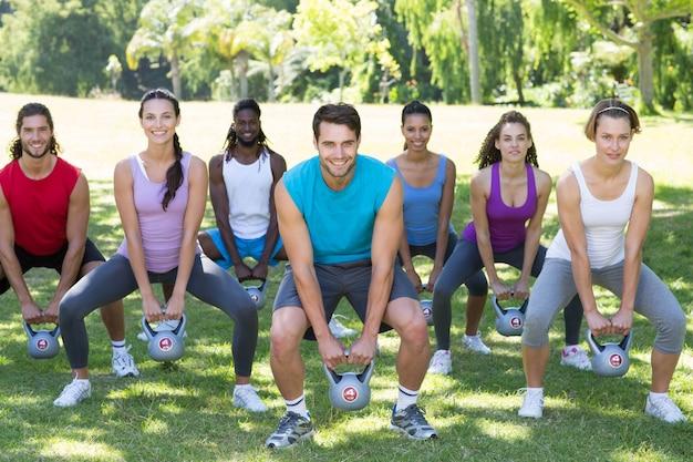 Grupo de fitness agachado no parque com sinos de chaleira