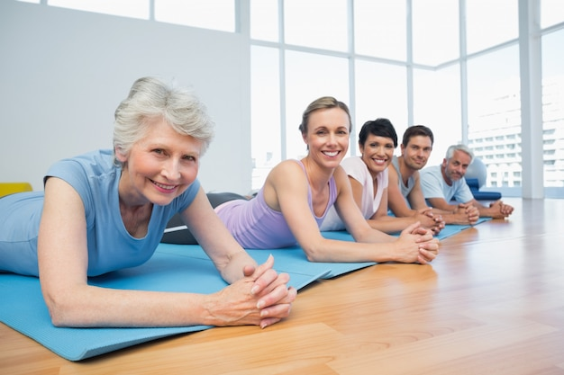Grupo de fitness deitado na fila na aula de yoga