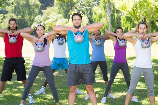 Grupo de fitness trabalhando no parque com sinos de chaleira