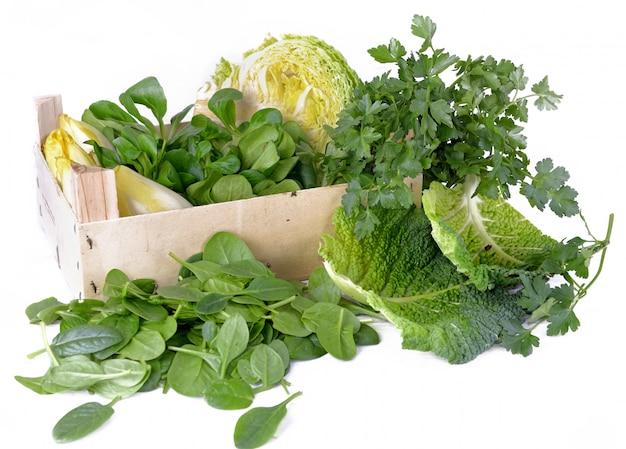 Grupo de folhas verdes de espinafre, salsa, repolho e outros legumes frescos em caixa