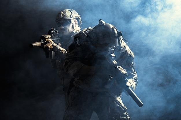 Grupo de forças de segurança em uniformes de combate com espingardas