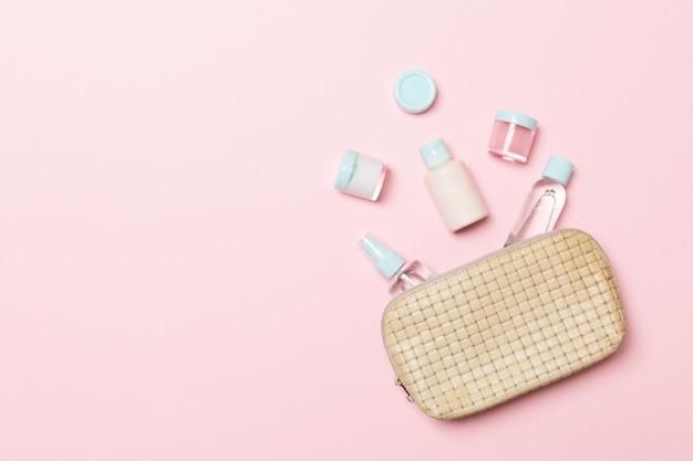Grupo de frascos de creme de beleza caiu fora do saco de cosméticos em rosa. espaço r. vista superior da pele