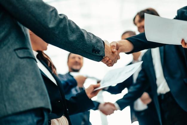Grupo de funcionários apertando as mãos em uma reunião de escritório