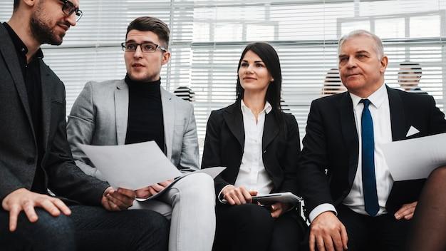 Grupo de funcionários com questionários sentado no saguão do escritório. conceito de negócios