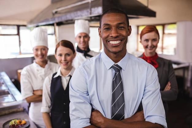 Grupo de funcionários do hotel em pé com os braços cruzados na cozinha