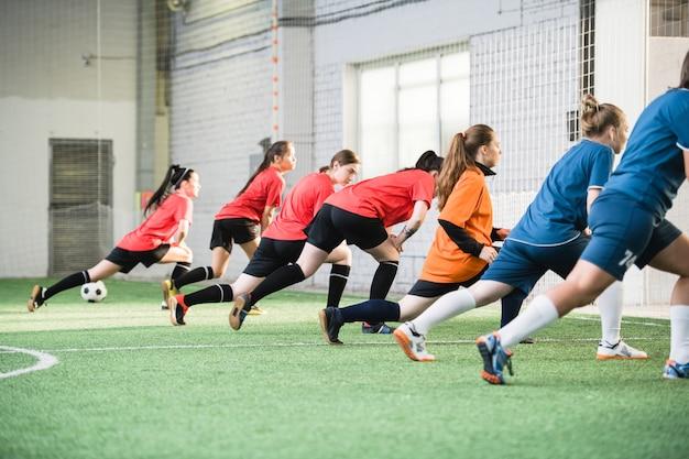 Grupo de futebolistas ativas com uniforme esportivo fazendo exercícios de alongamento no campo antes do jogo