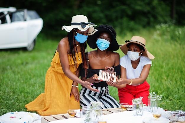 Grupo de garotas afro-americanas com máscaras faciais, comemorando a festa de aniversário ao ar livre com decoração durante a pandemia de coronavírus.