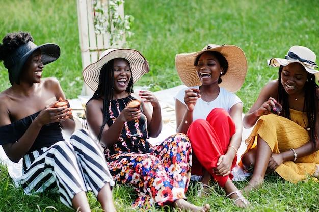 Grupo de garotas afro-americanas comemorando a festa de aniversário e comendo muffins ao ar livre