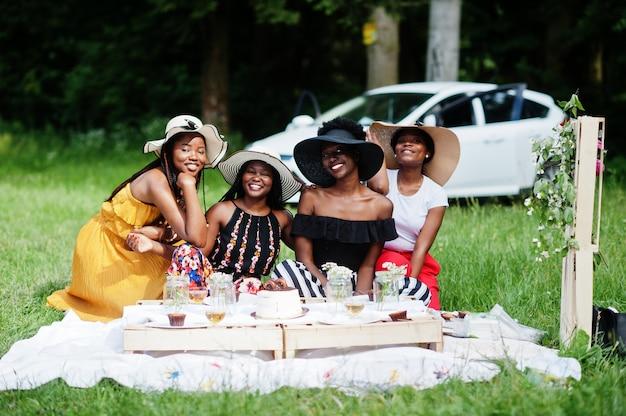 Grupo de garotas afro-americanas comemorando festa de aniversário e tilintando de copos ao ar livre