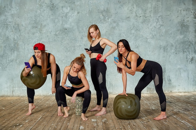 Grupo de garotas bonitas fitness em uma sala de fitness perto de uma parede cinza com um adereços para treinamento, emocionalmente falando ao telefone.
