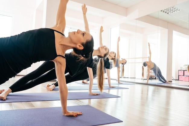 Grupo de garotas de esporte atraente em roupas esportivas malhando na sala de fitness.