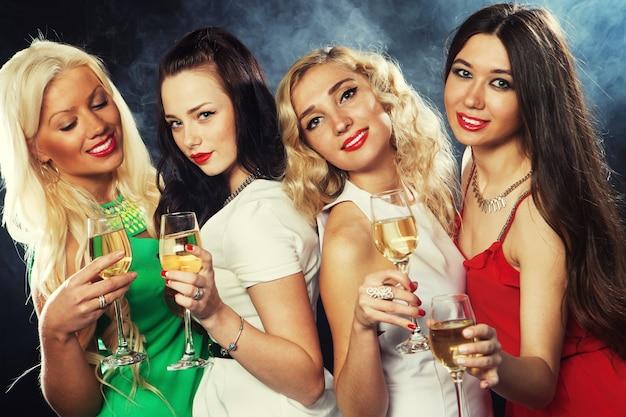 Grupo de garotas festeiras a tilintar taças com espumante