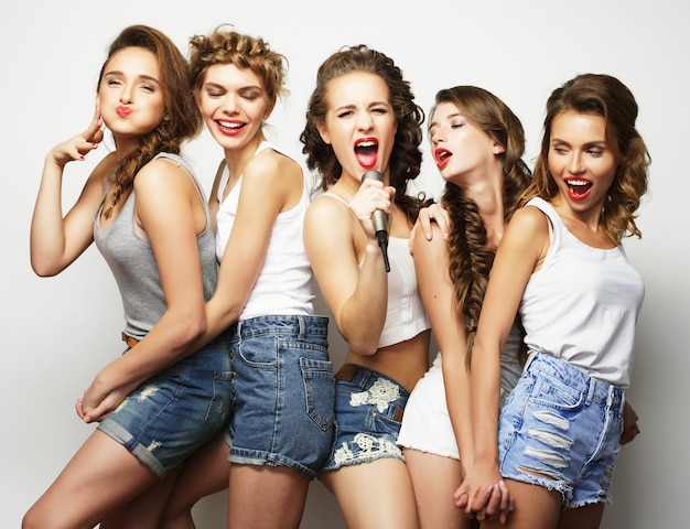Grupo de garotas lindas e elegantes e hipster cantando karaokê