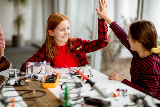 Grupo de garotinhas fofas programando brinquedos elétricos e robôs na sala de aula de robótica