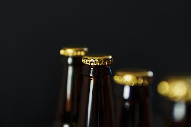 Grupo de garrafas de cerveja de vidro no fundo escuro com copyspace