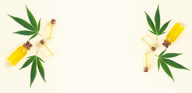 Grupo de garrafas de vidro com óleo de cannabis cbd, tintura de thc e folhas de cânhamo. vista superior, configuração plana