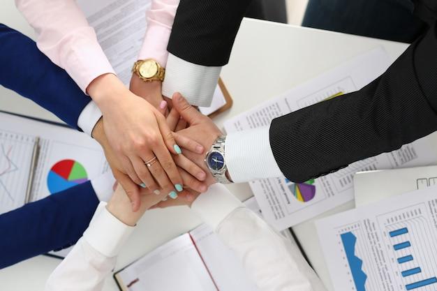 Grupo de gerentes, conectando as mãos no escritório, celebrando um bom negócio