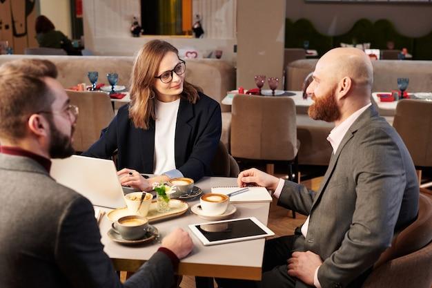 Grupo de gerentes de meia-idade sentado à mesa com café e discutindo ideias durante reunião de negócios no café
