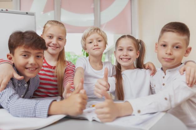 Grupo de giros crianças desenho juntos na aula de arte