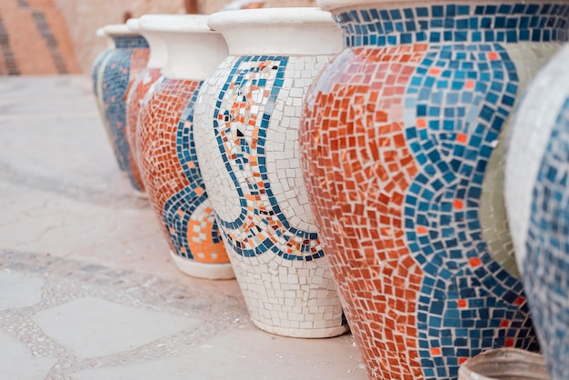 Grupo de grandes potes de barro com mosaico.