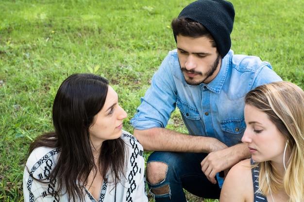 Grupo de grupo de estudantes relaxantes no campus da escola.