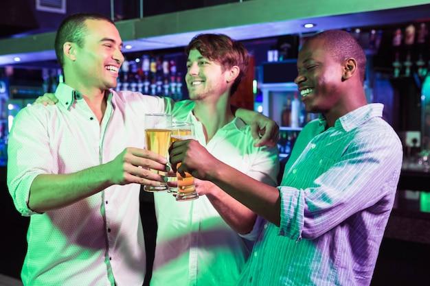 Grupo de homens brindando com copo de cerveja no bar