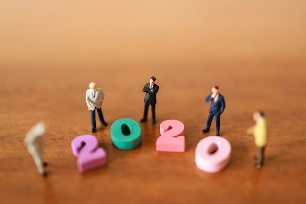 Grupo de homens de negócios em miniatura em pé ao redor de peças de madeira com número 2020