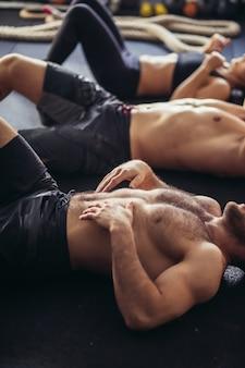 Grupo de homens e mulheres atléticos adultos realizando exercícios abdominais