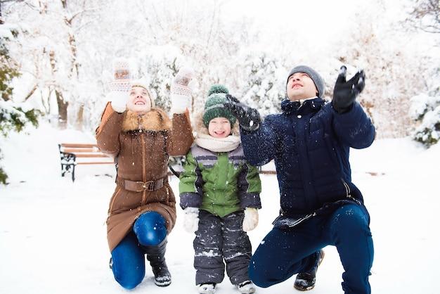 Grupo de homens e mulheres felizes se divertindo e brincando com a neve na floresta de inverno
