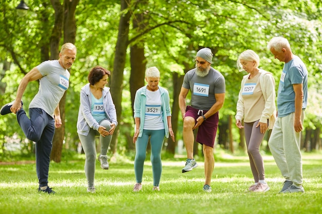 Grupo de homens e mulheres seniores participando de um treinamento de maratona, alongando as pernas antes de correr no parque