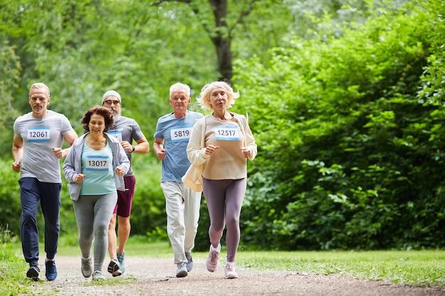 Grupo de homens e mulheres sêniors esportivos participando de uma maratona correndo ao longo do caminho do parque florestal, copie o espaço