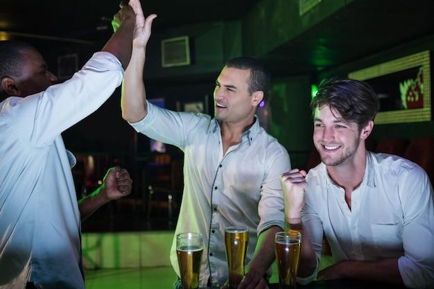 Grupo de homens festejando com copo de cerveja no bar