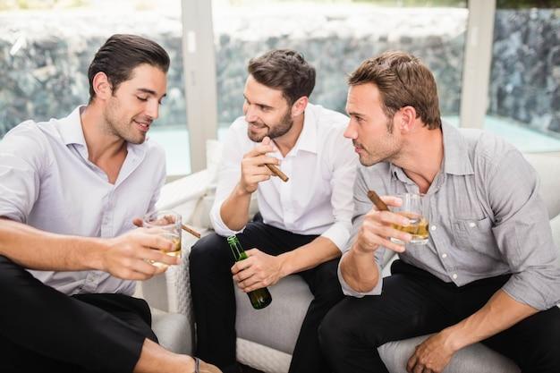 Grupo de homens fumando e bebendo enquanto discutia