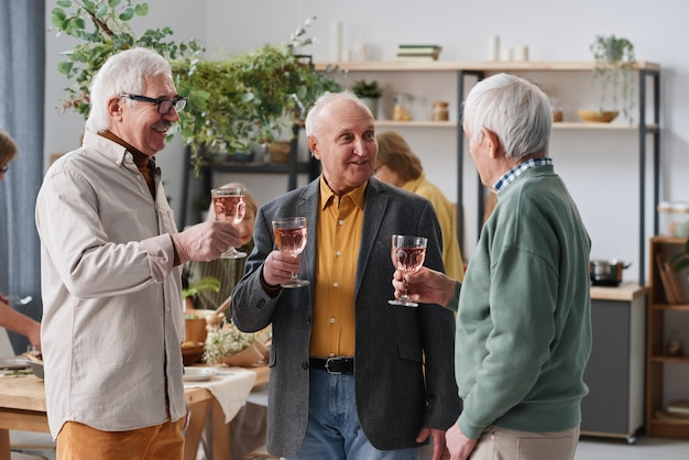 Grupo de homens idosos bebendo vinho tinto para conversar durante uma reunião