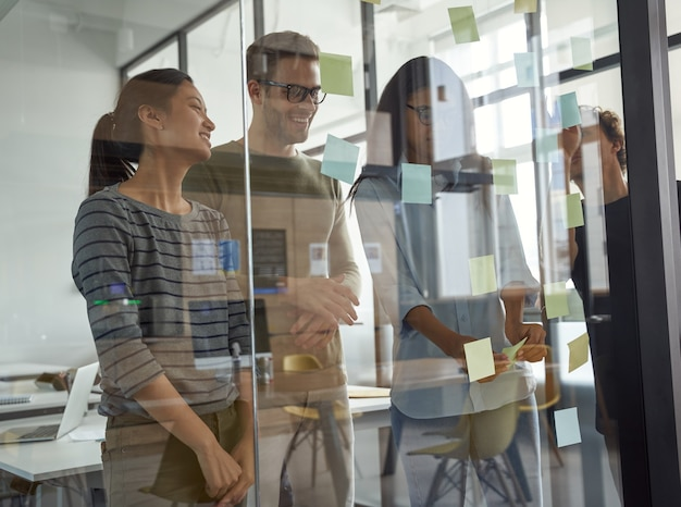Grupo de ideias de brainstorming de empresários felizes e criativos olhando para notas adesivas em vidro