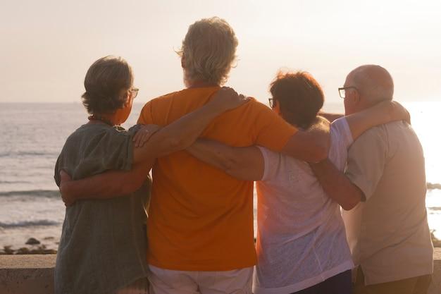 Grupo de idosos abraçados na praia olhando o mar com um lindo pôr do sol - família curtindo as férias