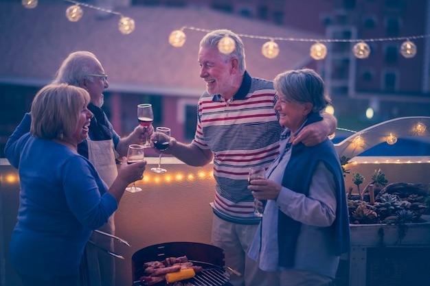 Grupo de idosos alegres e felizes se divertem juntos celebrando durante o jantar com churrasqueira e vinho tinto - véspera de ano novo ou conceito de festa para idosos