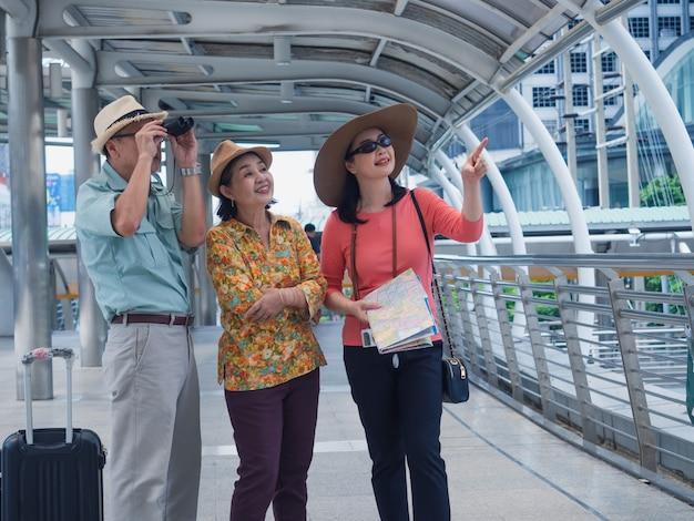 Grupo de idosos andando e conversando no caminho a pé na cidade, homem mais velho e mulher viajam em férias