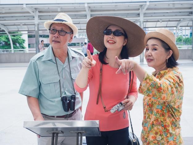 Grupo de idosos andando no caminho a pé na cidade, homem mais velho e mulher olhando para o mapa