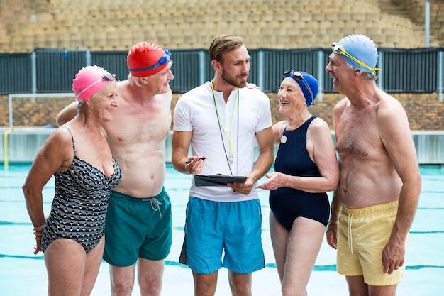 Grupo de idosos com instrutor em pé à beira da piscina