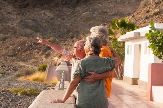 Grupo de idosos e maduros na praia olhando o mar ou o oceano se abraçaram e um deles está indicando algo