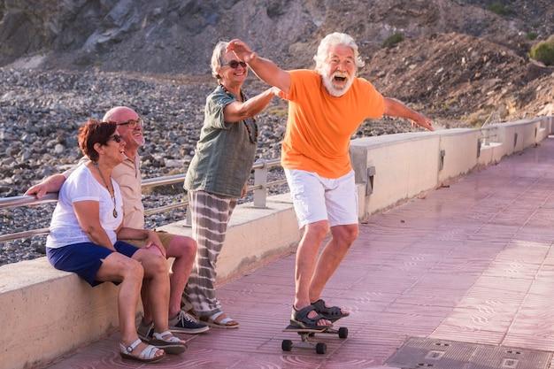 Grupo de idosos e pessoas maduras na praia se divertem olhando o velho andando de skate e rindo com cara de susto - mulher tocando o homem