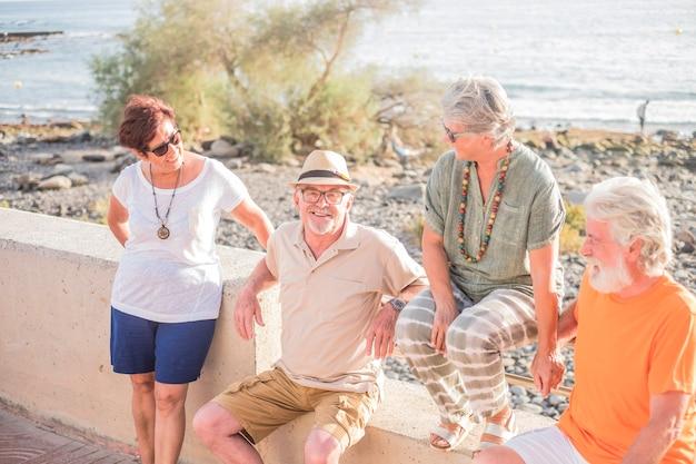 Grupo de idosos e pessoas maduras sentadas em um banco na praia - amizade feliz com dois casais de aposentados conversando e se divertindo