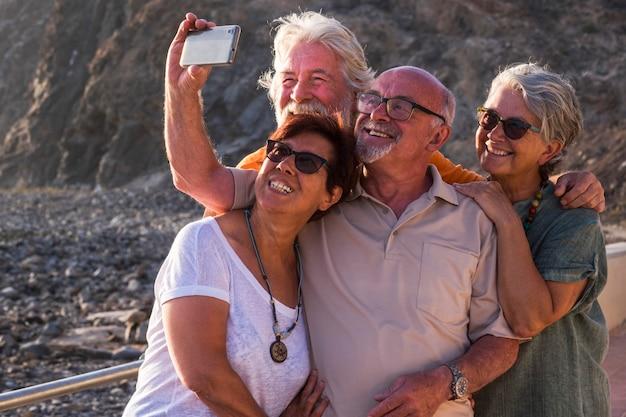 Grupo de idosos e pessoas maduras tirando uma selfie juntos na praia com as pedras no fundo - se divertindo juntos no pôr do sol