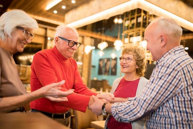 Grupo de idosos em pé em círculo e conversando