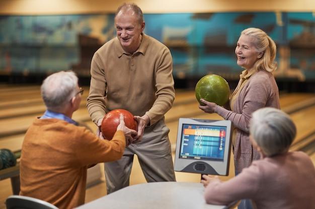 Grupo de idosos jogando boliche juntos enquanto desfrutam de entretenimento ativo na pista de boliche, copie o espaço